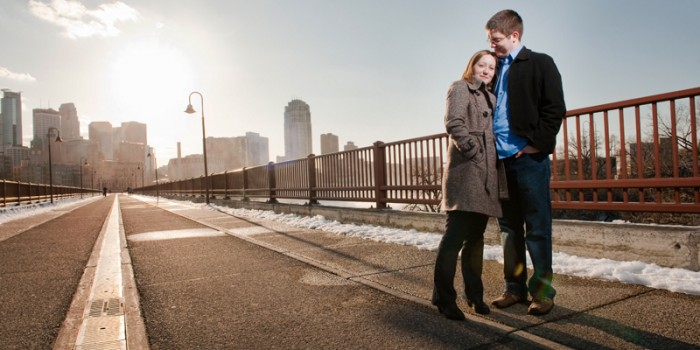 Minneapolis engagement photos on the stone arch bridge in downtown with skyline mn