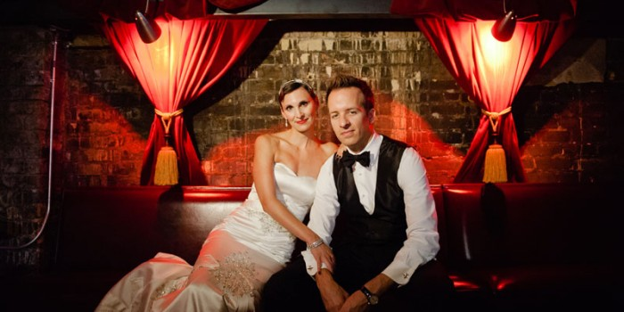 noir formal portrait of bride and groom with red curtains at Varsity Theater