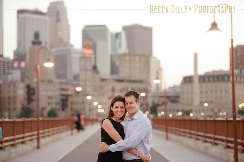 minneapolis couple portraits hugging on stone arch bridge at night