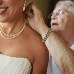 Bride's grandmother puts on pearls at Nicollet Island Inn Minneapolis