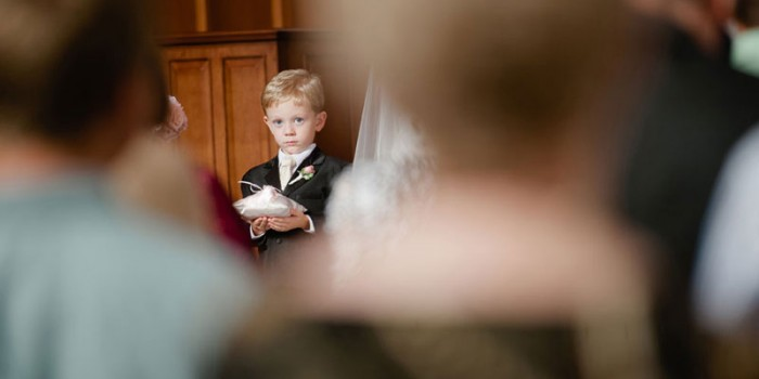 ringbearer looks through crowd during wedding ceremony