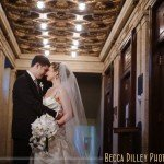 bride and groom under antique architectural lighting of Temple Israel in Minneapolis