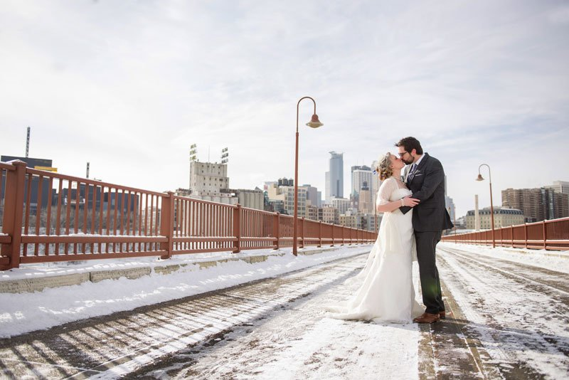 bride and groom with snow on stone arch bridge winter wedding in minneapolis