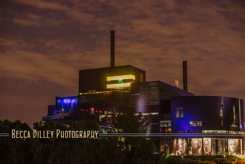 Silhouette of couple in Amber box of guthrie theater taken from the Stone Arch Bridge at night