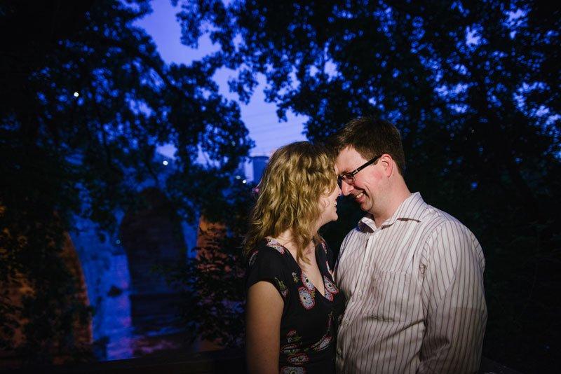 couple at night under stone arch bridge