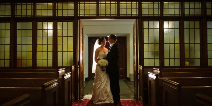 Bride and groom in front of windowed wall at Bethlehem Lutheran Church in Minneapolis MN