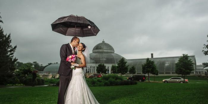 Ethiopian wedding bride and groom in rain with umbrella