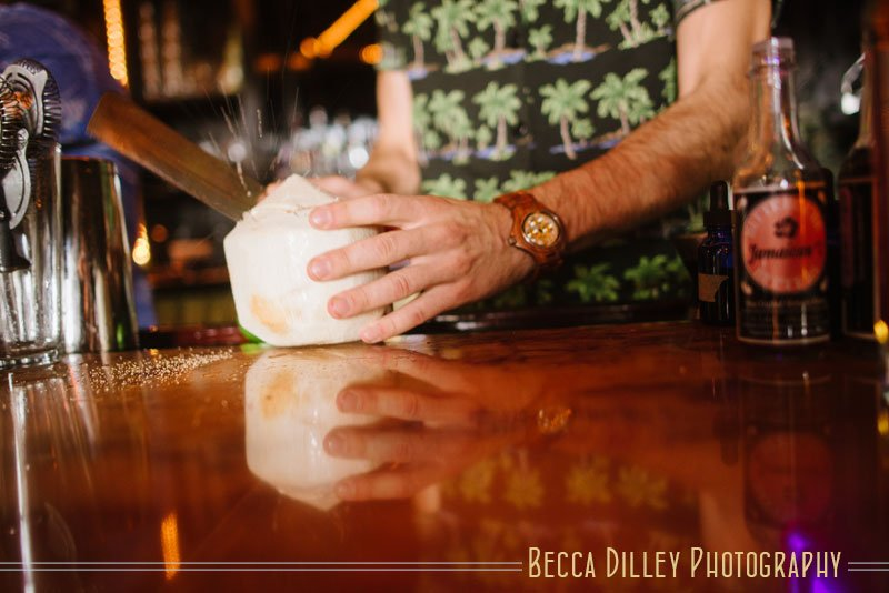 bartender opening coconut with a machete