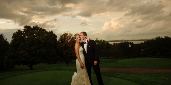 groom kisses bride at Madison wi wedding at black hawk country club at sunset