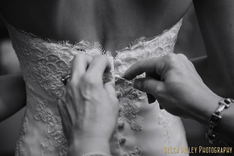 bride being buttoned into dress