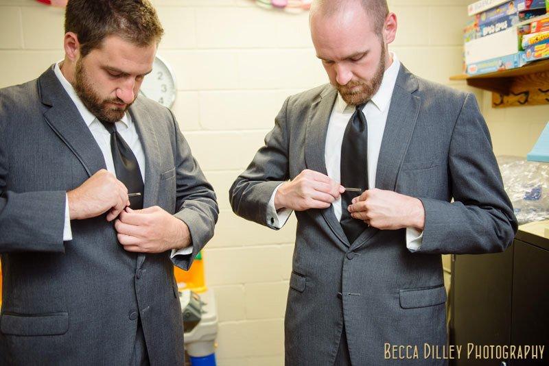 groomsmen putting on tie pins