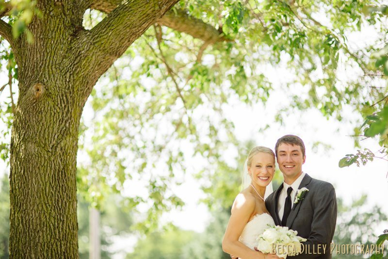 bride and groom under tree for summer wedding