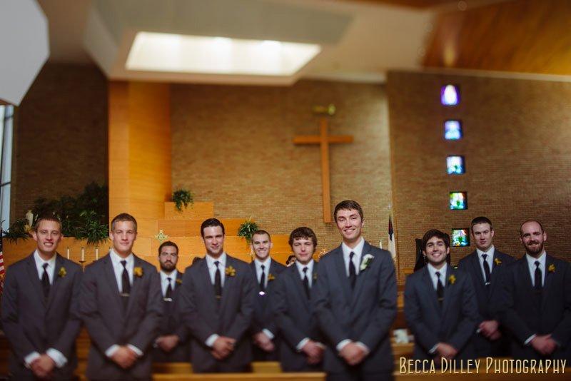 groom with 9 groomsmen in church pews