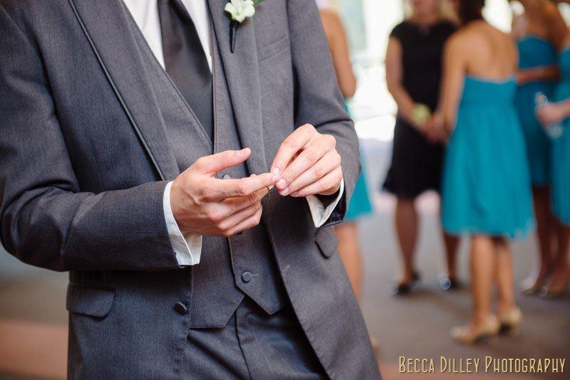 groom handling wedding rings