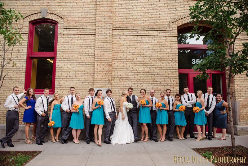 large wedding party in front of brick wall