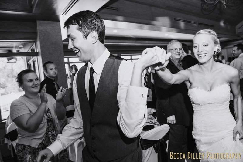 groom holds brides hand and runs into wedding reception at Mendakota Country Club