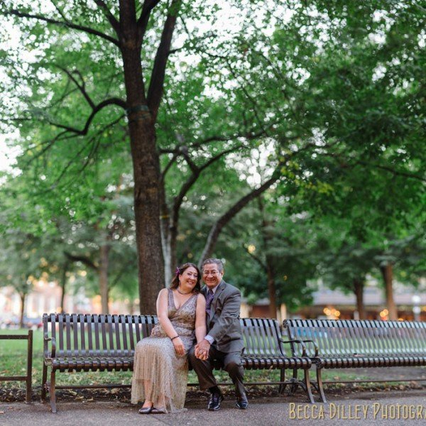 bride and groom sitting on bench at rice park panorama