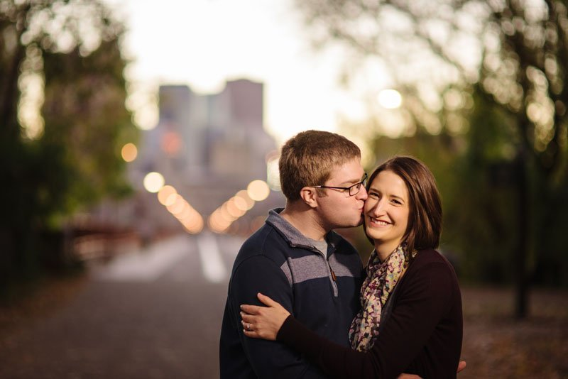 couple in front of stone arch bridge in evening