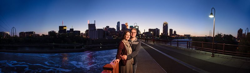 panorama of couple on stone arch bridge with minneapolis skyline at night and mississippi river