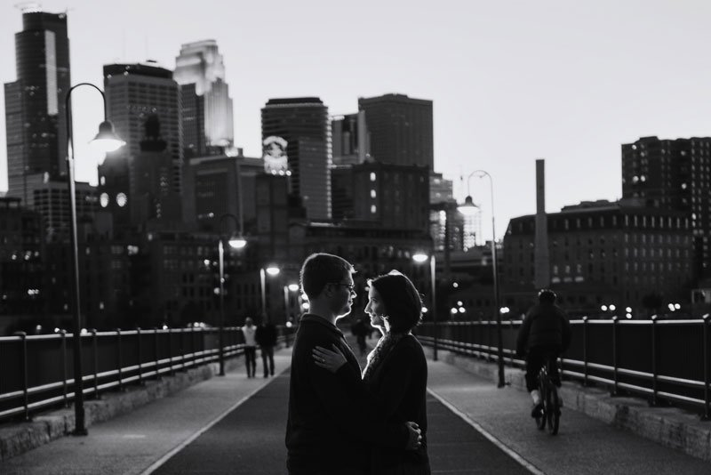 night portrait of couple on stone arch bridge with skyline behind them