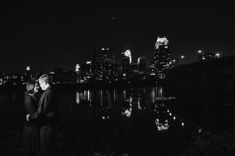 couple in front of minneapolis skyline at night reflected in mississippi river