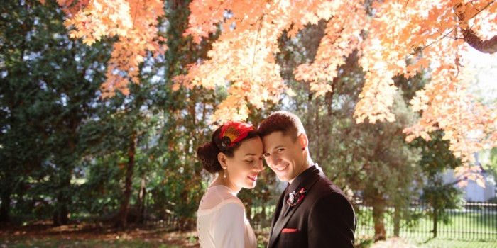 bride and groom under red autumn leaves in Minneapolis