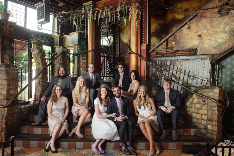 wedding party casually sitting on steps of loring pasta bar before wedding
