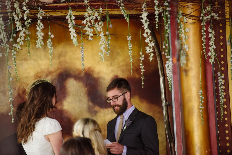 groom reads vows to bride at loring pasta bar wedding under hanging flowers