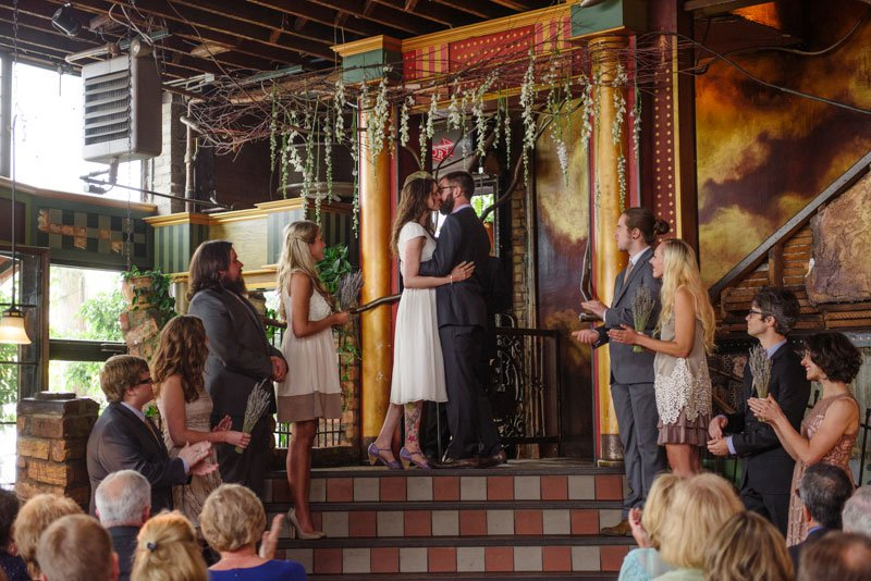 bride and groom kiss at loring pasta bar ceremony under hanging flowers