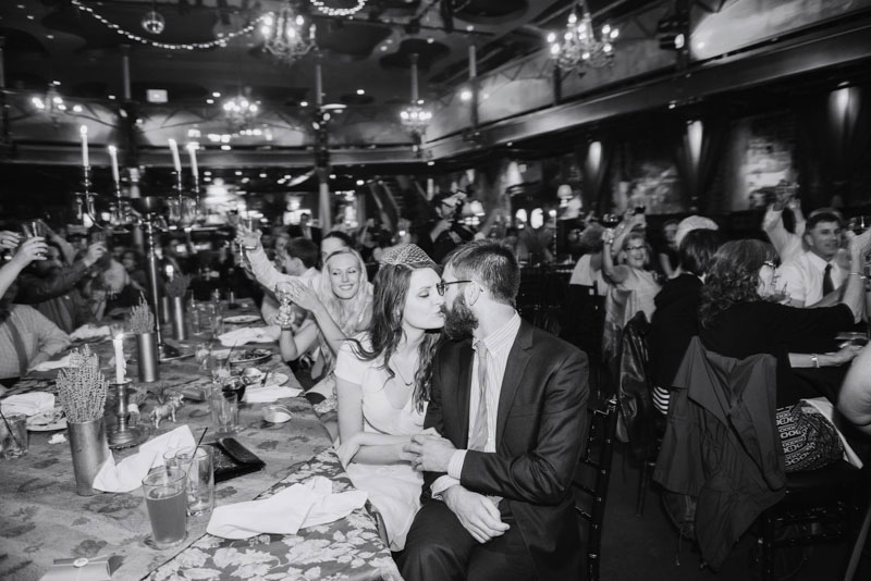 bride and groom kiss during toasts at varsity theater minneapolis