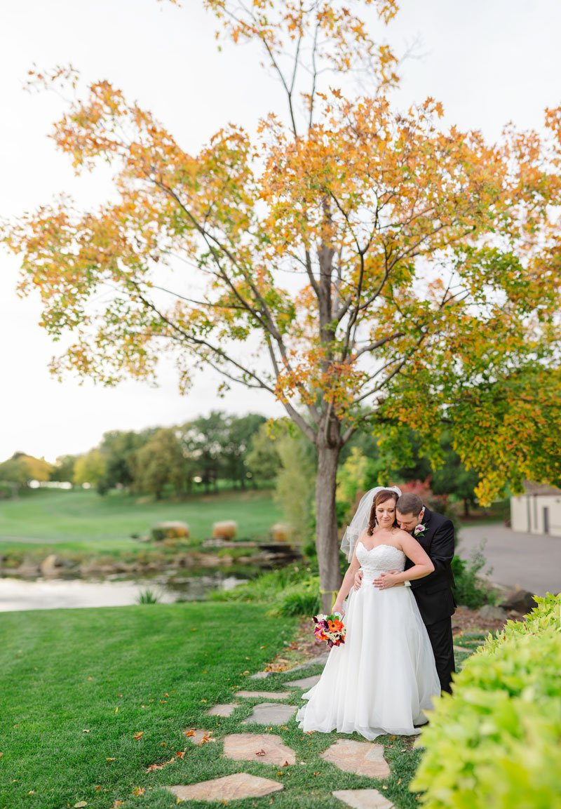 bride and groom under autumn tree at southview country club