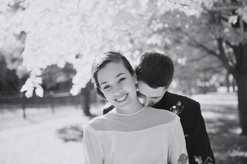groom kisses brides neck before elopement