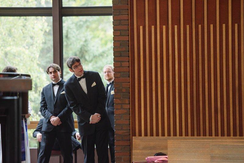 groom looks around wall for bride at weyerhaeuser chapel macalester college