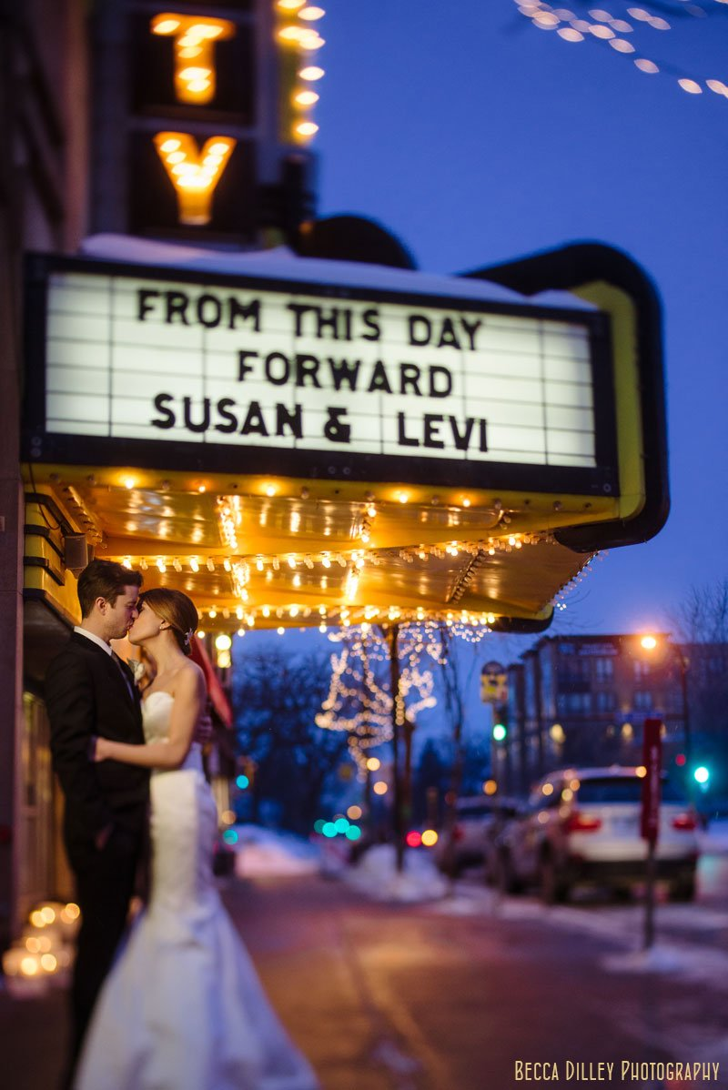 bride and groom under sign at varsity theater wedding