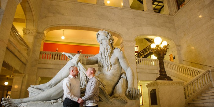 two grooms by father hennepin statue in Minneapolis City Hall