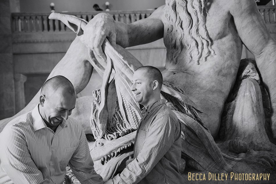 two grooms laugh by father hennepin statue in Minneapolis City Hall
