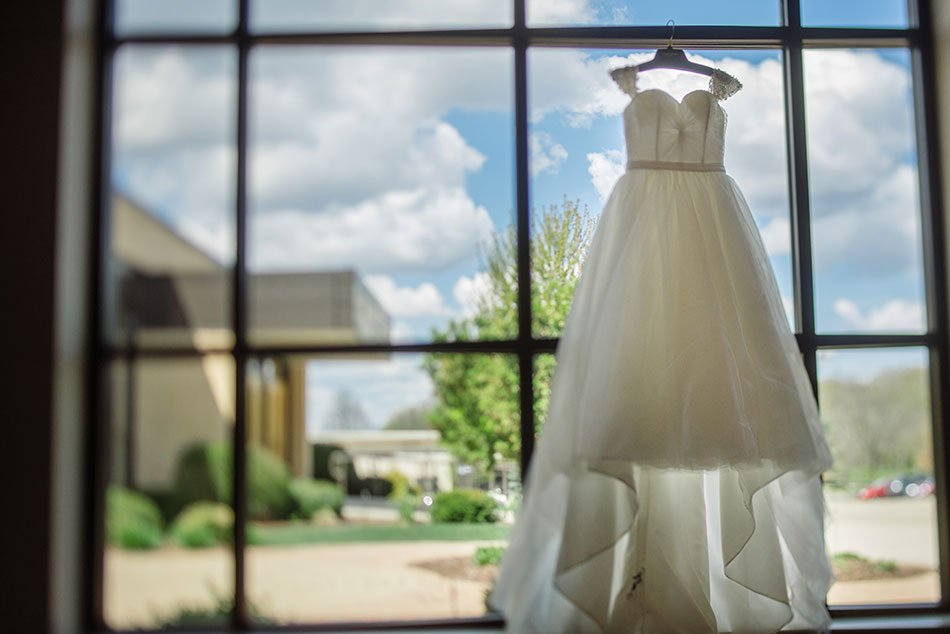 tilt shift photo of wedding dress hanging in window St Maria Goretti church wedding madison wi