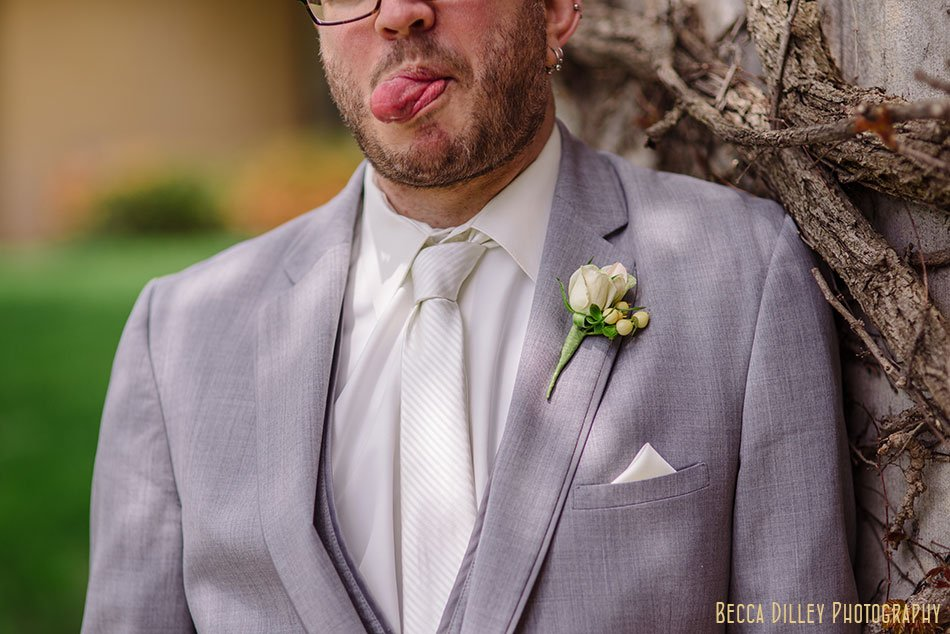 groom in grey suit sticks out tongue at St Maria Goretti church wedding madison wi