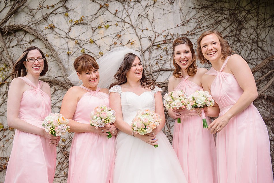 bride with 4 bridesmaids laughing in front of ivy wall at St Maria Goretti church wedding madison wi
