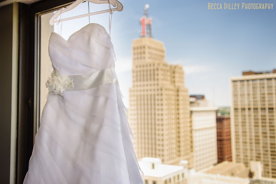 wedding dress hanging in window with st paul skyline behind