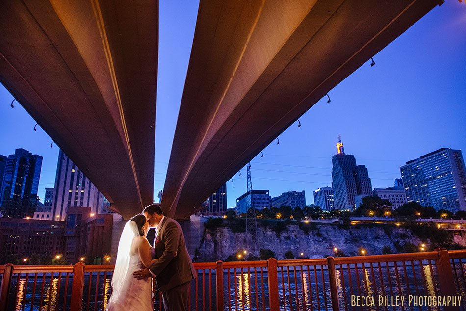 bride and groom under bridge at minnesota boat club with st paul skyline