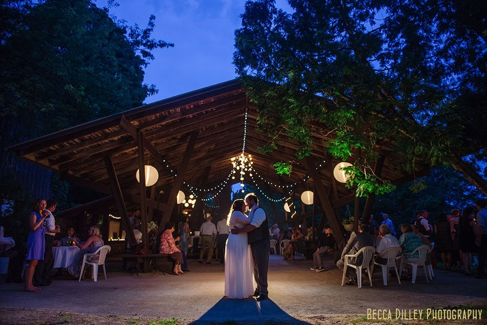 bride and groom in front of barn at night at hilltop in Spring Green WI