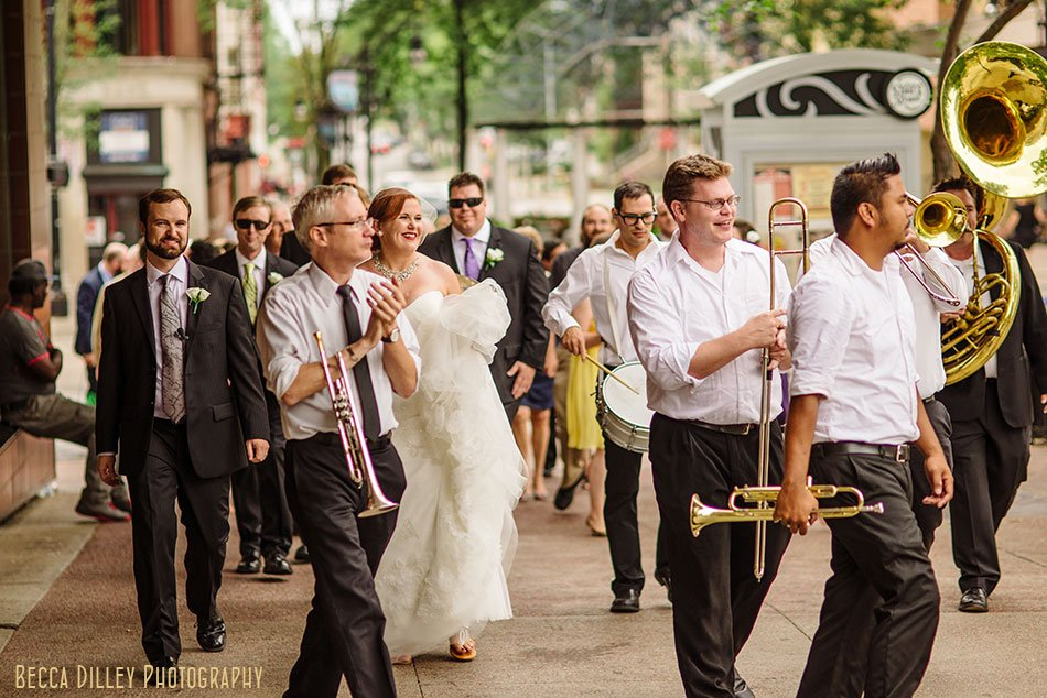 bride and groom walk around capitol with wedding with marching band second line around madison capitol
