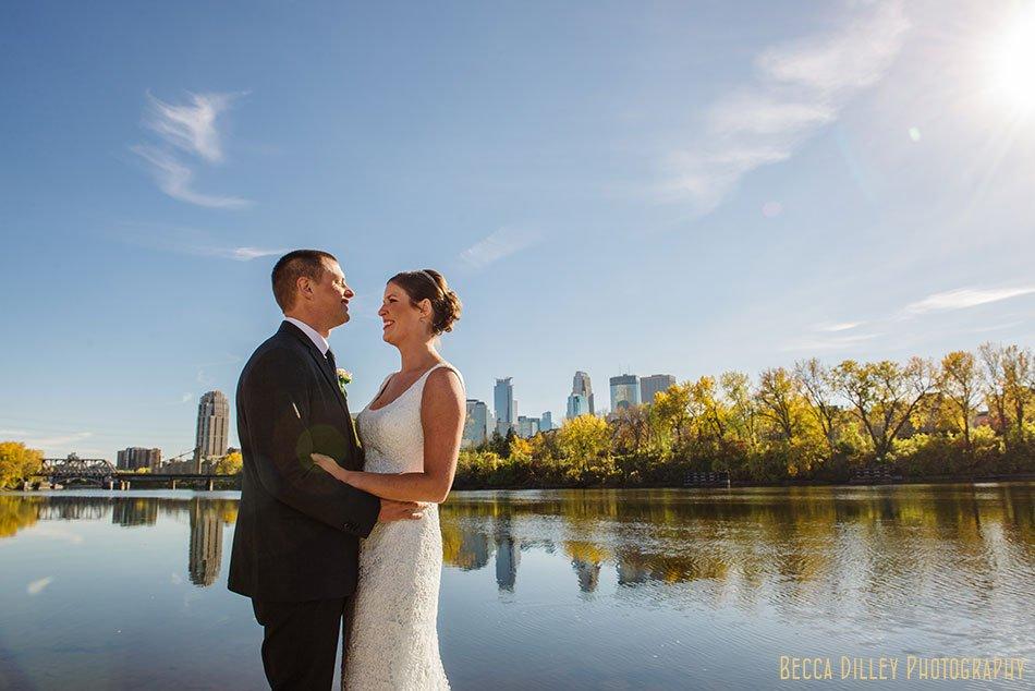 bride and groom on boom island with minneapolis skyline