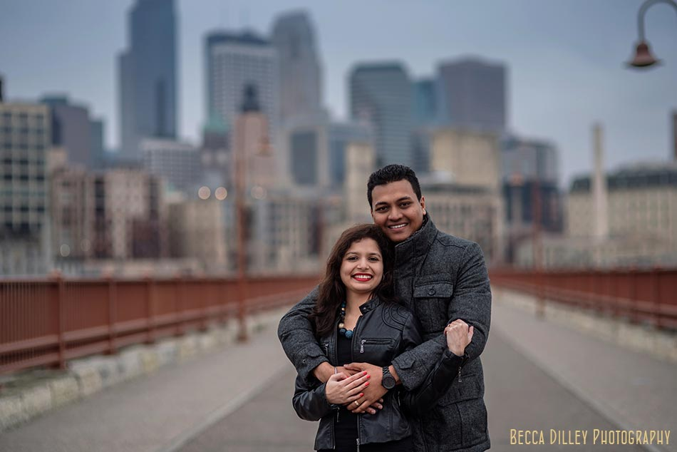 skyline minneapolis wedding photographer engagement photos at stone arch bridge in winter