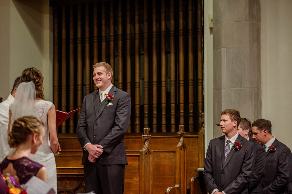 groom smiles at bride during ceremony St Lukes Episcopal church wedding minneapolis