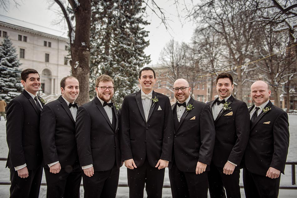6 groomsment outside St Paul Hotel winter wedding mn