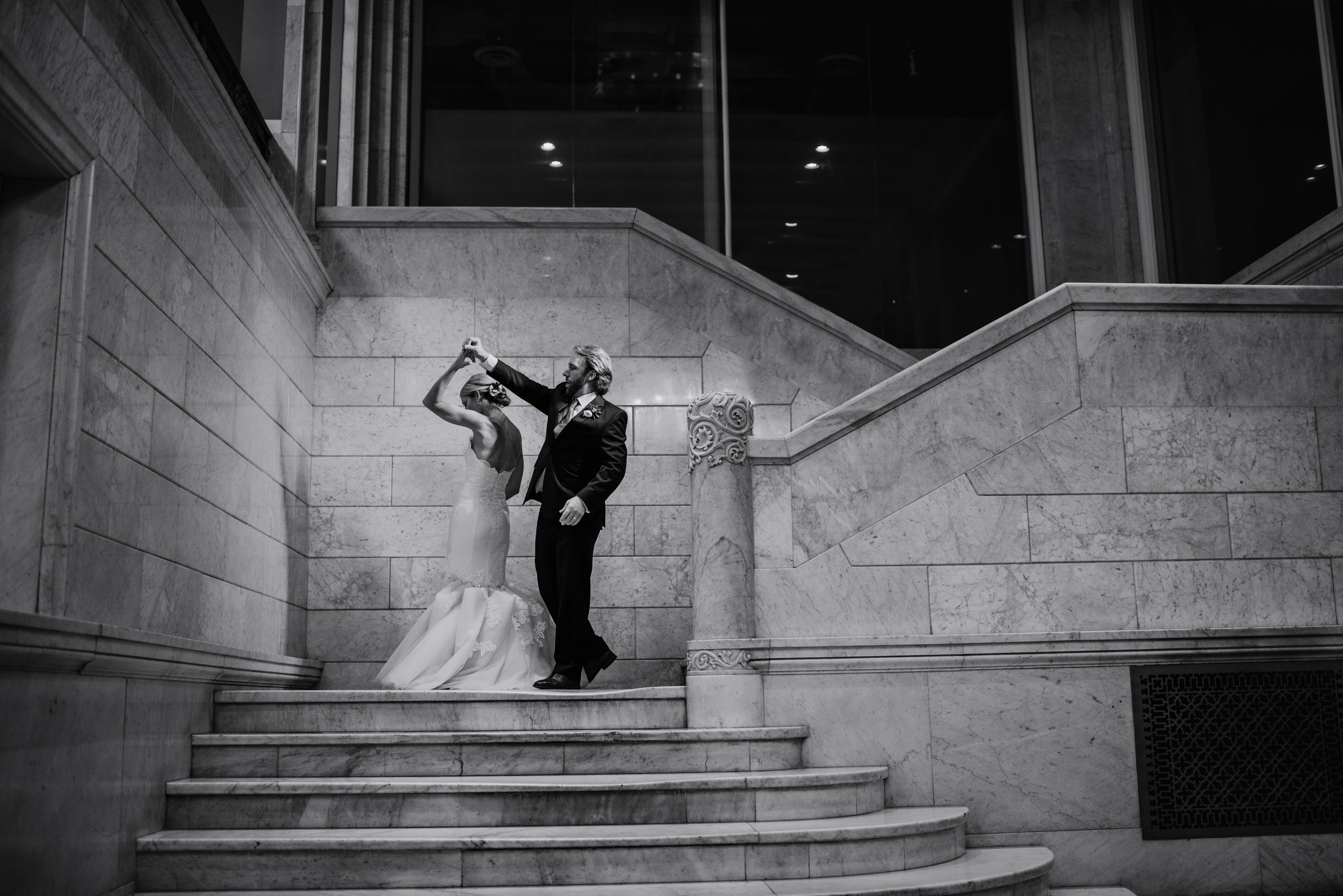 couple dance on marble staircase of lumber exchange lobby in downtown Minneapolis during wedding reception
