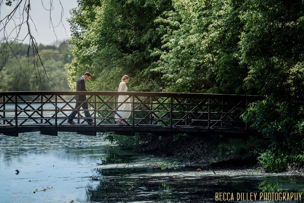 bride and groom walk across a bridge in minneapolis parks If you are planning your MN elopement