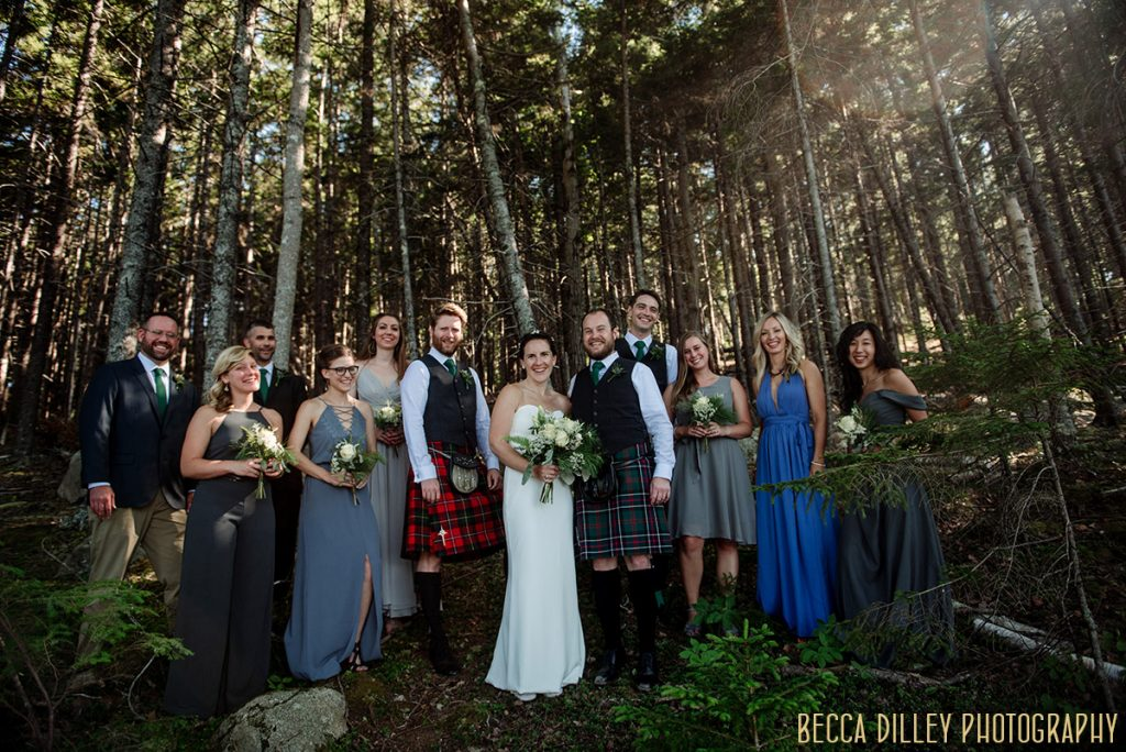 large wedding party in pine trees destination wedding by Acadia National Park in Maine